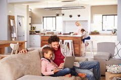 Avla genom att använda datoren med sonen, familj i bakgrund Royaltyfri Foto