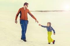Avla hjälp hans unga son som ger honom hans hand, snö royaltyfria bilder