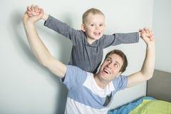 Avla lek med hans sonpojke på sängen hemma royaltyfri fotografi