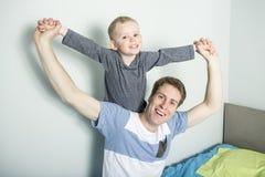 Avla lek med hans sonpojke på sängen hemma royaltyfri bild
