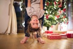 Avla med daugter på julgranen som rymmer henne uppochnervänd arkivfoton