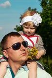 Avla med den lilla blonda dottern på hans skuldror Royaltyfria Bilder