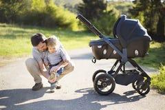 Avla med den lilla sonen och behandla som ett barn dottern i sittvagn Soligt parkera arkivfoton