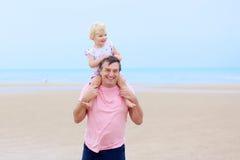 Avla med dottern som har gyckel på stranden Arkivfoton