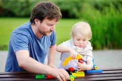 Avla med hans litet barnson som spelar med färgrika plast- kvarter Royaltyfri Bild
