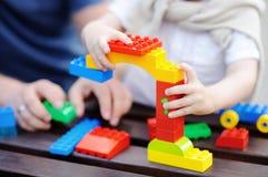 Avla med hans litet barnson som spelar med färgrika plast- kvarter Royaltyfri Foto
