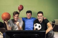 Avla med hans söner som håller ögonen på sporten på television royaltyfri foto