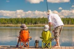 Avla med hans son och dotter på en träpir i sjön fi Royaltyfri Bild