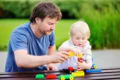 Avla med hans son som spelar med färgrika plast- kvarter Arkivfoton