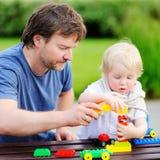 Avla med hans son som spelar med färgrika plast- kvarter Arkivbilder