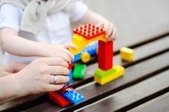 Avla med litet barnsonen som spelar med plast- kvarter Arkivbild