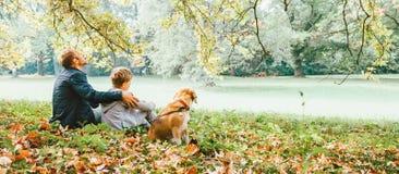 Avla med sonen går med beaglehunden och tycker om varm höstdag royaltyfria foton
