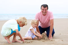 Avla med ungar som har gyckel på stranden Arkivbild