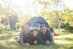 Avla modern och sonen som ligger utanför tältet på campingplatsen Royaltyfri Bild