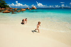Avla och årig pojke som två spelar på stranden Royaltyfri Fotografi