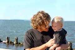 Avla och behandla som ett barn att skratta på sjön Royaltyfri Bild