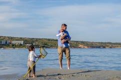 Avla och behandla som ett barn och lilla barnet som spelar på den sandiga stranden royaltyfri foto