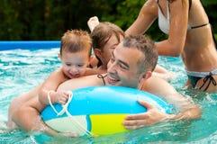 Avla och hans barn som har gyckel i simbassängen i summe Arkivfoton