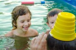 Avla och hans barn som spelar i simbassängen Arkivbild