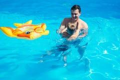 Avla och hans son som har gyckel i simbassängen arkivbild