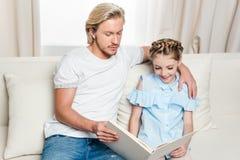 Avla och le dotterläseboken på soffan hemma Arkivfoto