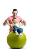 Avla och lura sonen som har gyckel med den gymnastiska bollen Fotografering för Bildbyråer