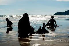 Avla och två pojkar som spelar på stranden fotografering för bildbyråer