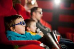 Avla och två barn, pojkar som håller ögonen på tecknad filmfilm i bion Arkivfoton
