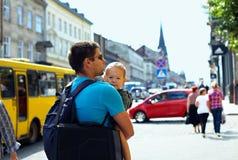 Avla sonen som går till och med den fullsatt stadsgatan Arkivfoto