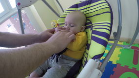 Avla tar nyfött behandla som ett barn pojken eller flickan i gunga hemma 4K arkivfilmer