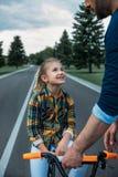 Avla undervisa hans lyckliga dotter hur man rider en cykel Arkivbilder