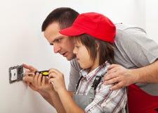 Avla undervisningsonen grunderna av elektriskt arbete runt om houen Royaltyfri Foto