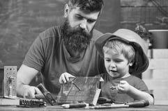 Avla, uppfostra med skägget som undervisar den lilla sonen att använda grovt sulstift och hammaren Manligt arbetsuppgiftbegrepp P arkivfoton