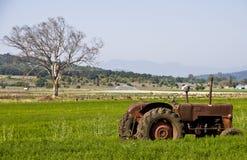 Avlagd traktor i fält Arkivbild