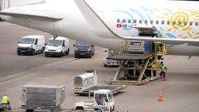 Avlastning av bagagebehållare från flygplanet arkivfilmer