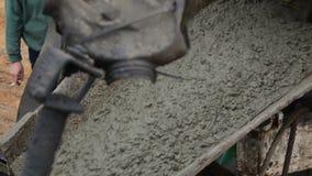 Avlastning av den nya cementblandningen från blandarelastbilen in i den konkreta sprejaren arkivfilmer