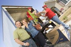 Avlastning av leveransen Van In Front Of House Arkivfoto