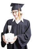 Avläggande av examenkvinnastudent med glasögon som rymmer spargrisen med Royaltyfri Foto