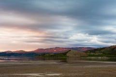 avlägsen glödande ljus bergsolnedgång yukon Arkivfoton