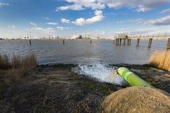 Avloppsvattenrör och raffinaderi på floden Fotografering för Bildbyråer