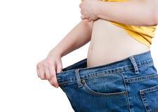 Avmagrad flicka som försöker på gammal jeans för stort format Arkivfoton