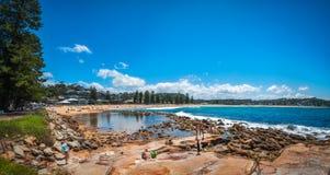 People on the shore at Avoca Beach, Australia. Avoca Beach, Central Coast, Australia - November 12, 2017: Kids playing and People enjoying a beautiful sunny day Stock Image