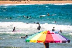 Colorful umbrella at Avoca Beach, Australia. Avoca Beach, Central Coast, Australia - November 12, 2017: One person exploring the rocky cliffs on a beautiful Royalty Free Stock Images