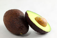 Avocado. Half laying on the white background with a slided half next to it Royalty Free Stock Photos
