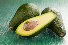 Avocado. Photo of cutted avocado fruit on green glass table Stock Images