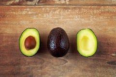 Avocado affettato fresco Concetto vegetariano dell'alimento Intero di avocado e due metà in una fila su fondo marrone immagine stock