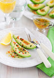Avocado appetizer. Avocado with orange sauce with lemon zest, chilli and parsley, selective focus Stock Images