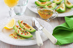 Avocado appetizer. Avocado with orange sauce with lemon zest, chilli and parsley, selective focus Royalty Free Stock Photography