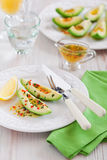 Avocado appetizer. Avocado with orange sauce with lemon zest, chilli and parsley, selective focus Royalty Free Stock Image