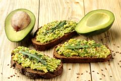 Avocado and arugula sandwiches and other ingredients on a natural wooden table. Sandwich with avocado puree stock photos